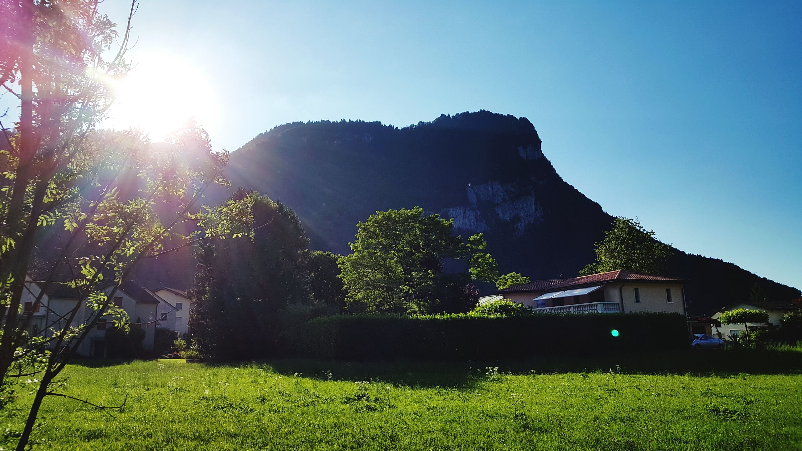 sun, clear sky, sunlight, grass, lens flare, sunbeam, tree, mountain, built structure, tranquility, tranquil scene, nature, beauty in nature, blue, landscape, building exterior, architecture, scenics, sunny, growth