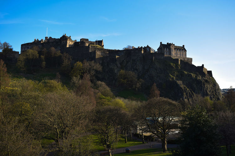 Low angle view of edinburgh castle on mountain against blue sky
