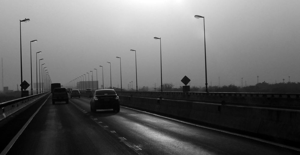 Cars on highway against sky in city