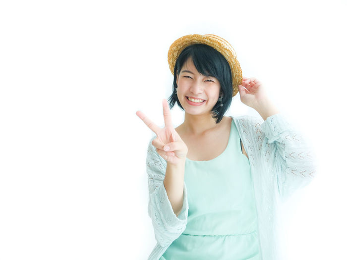 Portrait of smiling young woman showing peace sign against white background