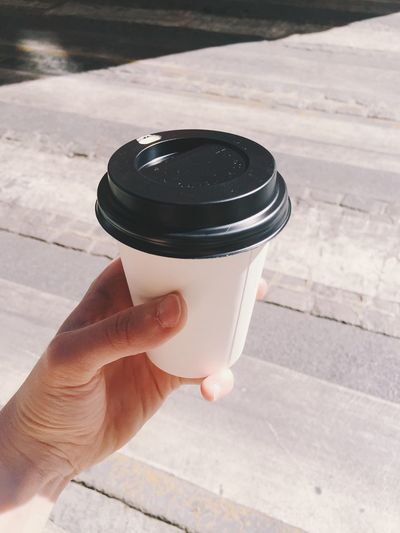 Cropped Image Of Hand Holding Disposable Coffee Cup