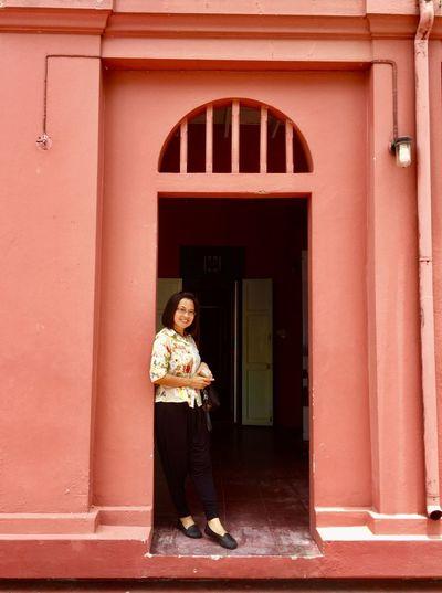 Woman standing against door of building