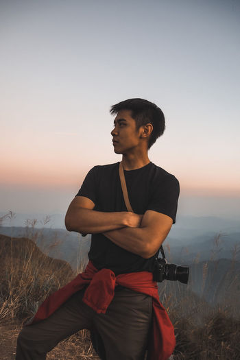 Young man sitting on land against sky during sunset
