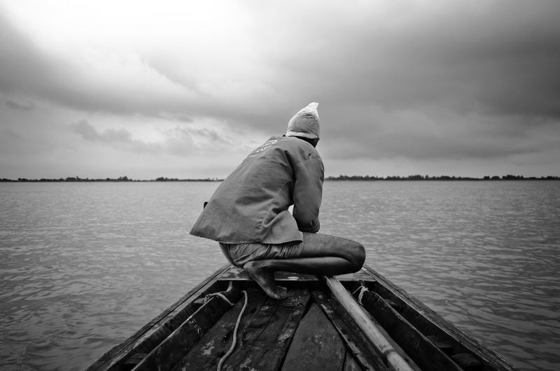 Rear View Of Man On Boat In Sea Against Sky