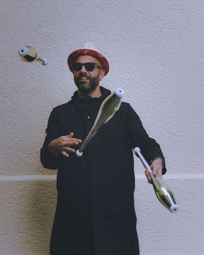 Young Man Wearing Sunglasses Juggling Against Wall