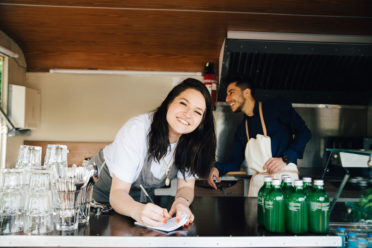 Portrait of smiling young woman standing in restaurant
