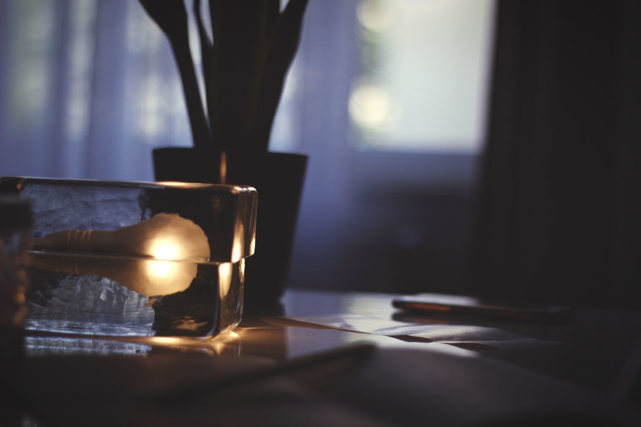 indoors, table, illuminated, candle, burning, fire - natural phenomenon, lighting equipment, flame, nature, fire, no people, selective focus, heat - temperature, close-up, glowing, focus on foreground, sunlight, window, glass - material, home interior, dark, electric lamp, tea light
