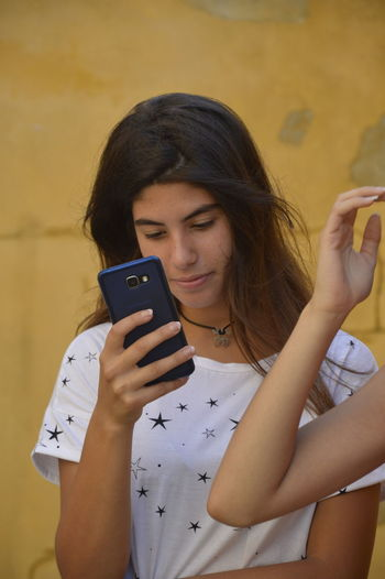 Woman Using Mobile Phone While Standing Against Wall