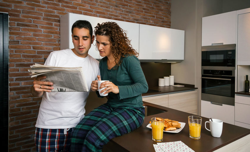 Couple having breakfast in the kitchen and reading the newspaper Horizontal Copy Space Informal Modern Brick Wall Croissant Serious Portrait Biscuits Sharing  Leisure Together Orange Juice  Coffee Indoor Real Two Young Woman Curly Hair Wife Standing People Married Man Male Lifestyle Husband Talking Caucasian Home Morning Sunday Girl Female Entertainment Watching Kitchen Looking Weather Forecast News Newspaper Reading Breakfast Pajama Couple Interested