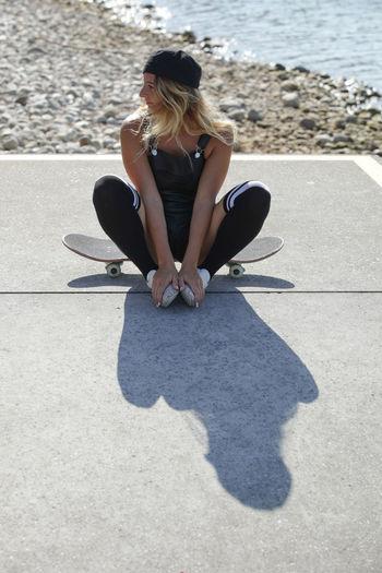 Woman sitting on skateboard at beach