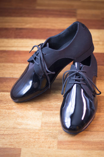 High angle view of formal shoes on hardwood floor