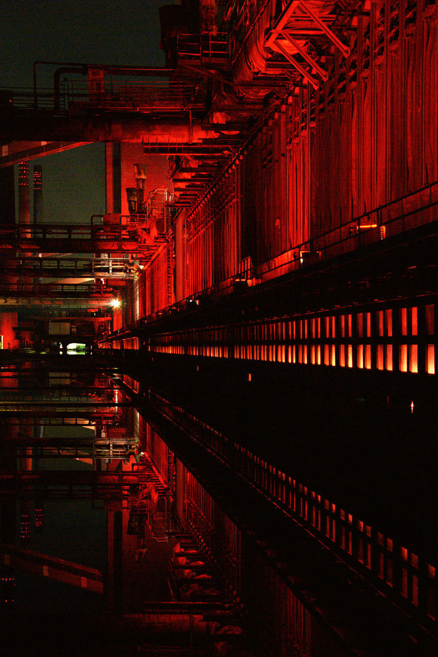 illuminated, architecture, built structure, no people, night, reflection, water, transportation, industry, building exterior, red, public transportation, outdoors, building, nature, light - natural phenomenon, factory, rail transportation, nightlife