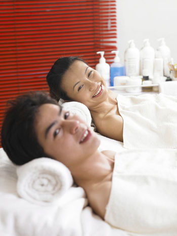 Couple Relaxing on Massage Table Business Stories Adult Beauty Spa Care Cople Day Enjoying Life Indoors  Lifestyles Love Lying Down Massage Mid Adult Women Pampering People Real People Relaxation Smiling Spa Togetherness Wellbeing Women Young Adult Young Women