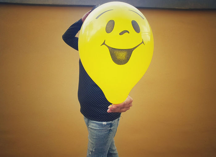 Midsection of man holding yellow balloon with anthropomorphic face against wall