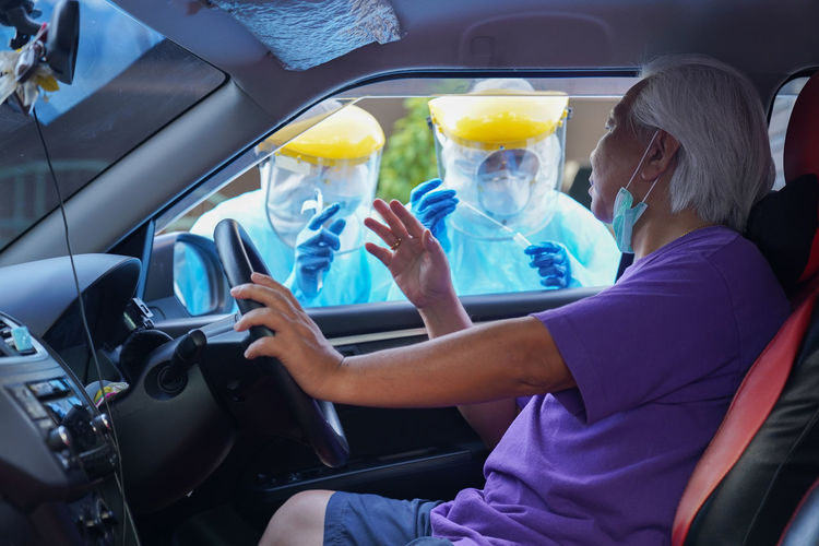 Doctor or nurse wearing ppe n95 mask face shield and personal car road screening for covid-19 virus