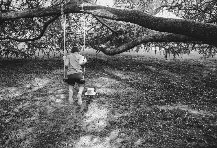 Rear view of boy enjoying swing at park
