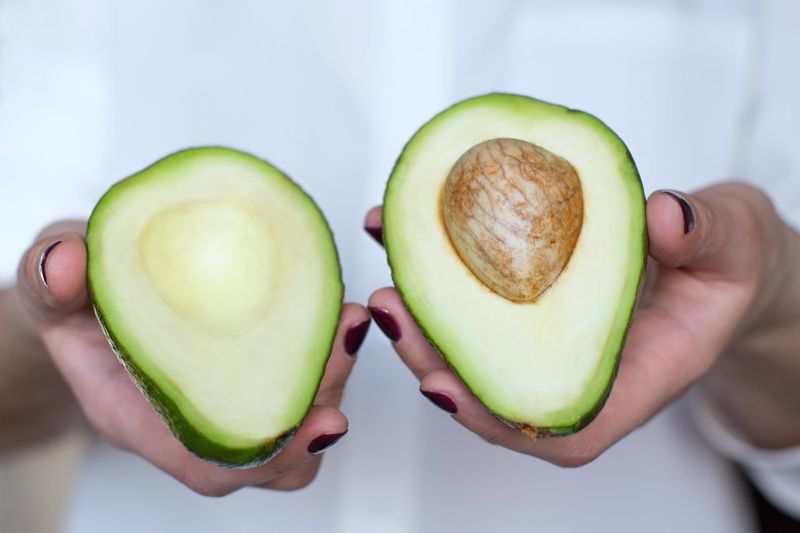 Young women holding two halves of avocado Preparation  Vegetarian Food Vegan Raw Food Organic Vitamin Dieting Breakfast Snack Time! Nutrition Food And Drink Human Hand Healthy Eating Holding Wellbeing Halved Freshness Fruit Green Color Avocado Healthy Lifestyle
