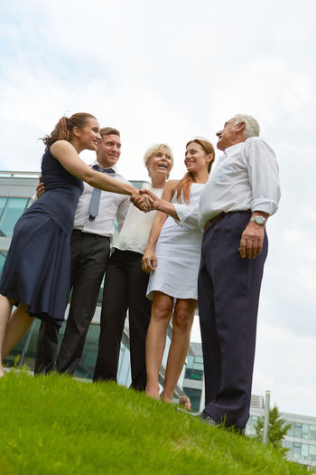 Low angle view of business people shaking hands with colleague against sky