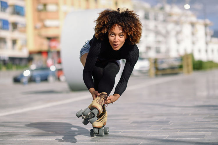 Portrait Of Woman Roller Skating On Sidewalk In City