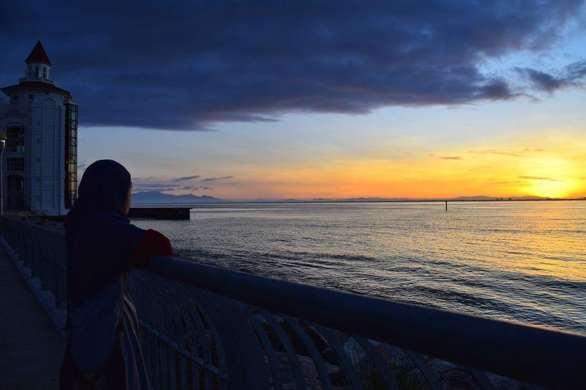 Admiring beautiful sunrise. Sunrise Dawn People Horizon Water Sea Beach Shadow Silhouette Wave Sand Reflection Seascape Romantic Sky Coastal Feature Coast Coastline Ocean Calm Rocky Coastline The Traveler - 2018 EyeEm Awards
