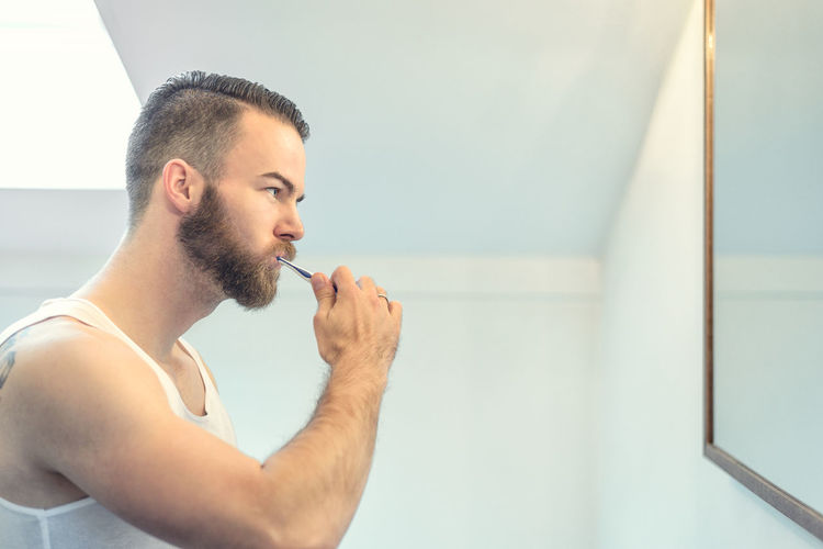 Side View Of Young Man Brushing Teeth In Bathroom