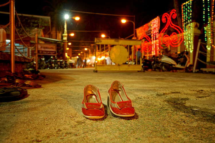 Shoes on footpath with illuminated decorations at night