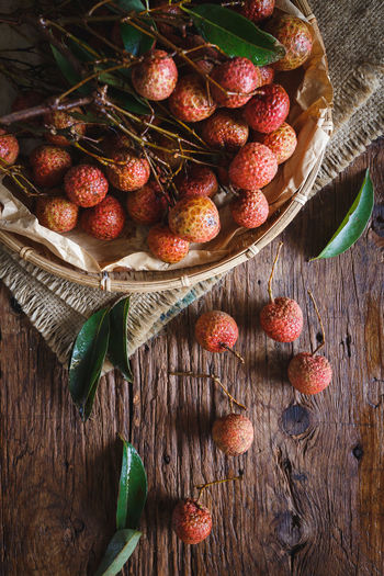 High angle view of lychees and wicker basket on wooden table
