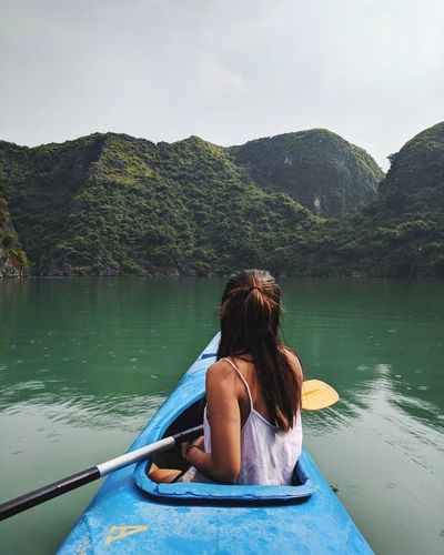 Rear view of woman kayaking on lake against mountains