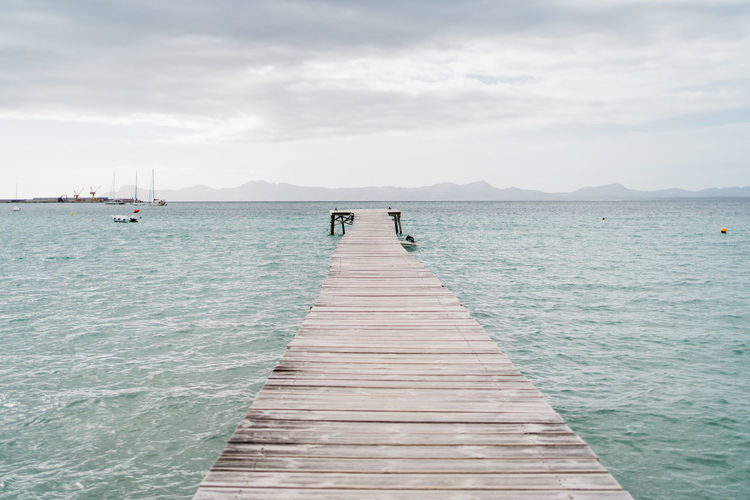 Beach of alcudia in spain with a pier