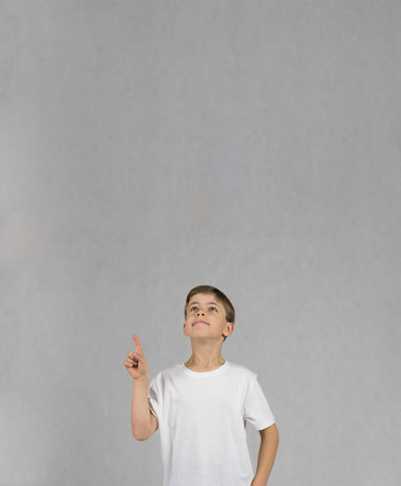 Young boy wearing white t-shirt smiling and looking up with his hand and figer up like having an idea Childhood Copy Space Day Idea Indoors  One Person People Studio Shot