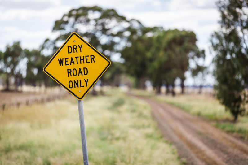 A yellow road sign along a dirt road in rural New South Wales, Australia. Australia Australian Landscape Australian Outback Country Lost Off The Beaten Track Outback Trees Wet Weather Countryside Danger Dirt Road Dry Weather Dusty Focus On Foreground Landscape Mud Outback Australia Road Sign Roadside Rural Scene Slippery When Wet Survival Warning Sign Yellow