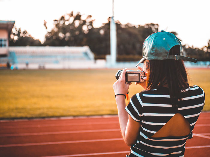 Rear view of woman photographing with camera at sports track