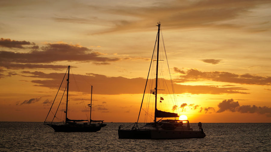 Silhouette sailboats on sea against sky during sunset