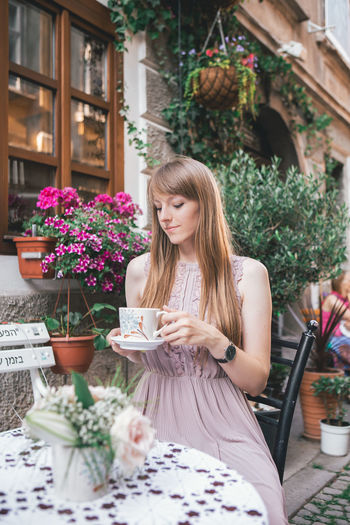 Young woman sitting outside of Coffee Shop Real People One Person Long Hair Lifestyles Hair Young Women Leisure Activity Women Young Adult Hairstyle Plant Sitting Beauty Drink Smiling Flower Table Holding Beautiful Woman Outdoors Fashion Blogger Watch Urban Urbanphotography City Ljubljana Slovenia Portrait Portrait Of A Woman Woman Casual Clothing Casual Look