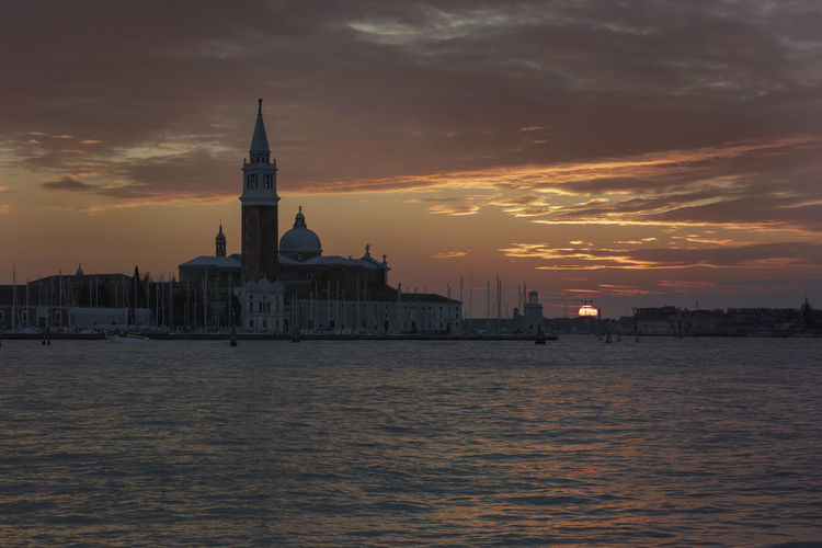 San giorgio maggiore by grand canal against cloudy sky during sunset