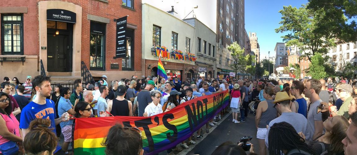 Greenwich Village, NYC, June 13, 2016: LGBT rights advocates gather at a vigil at the historic Stonewall Inn, in Greenwich Village, Manhattan, to honor the victims of the mass shooting at a gay club in Orlando, Florida. Architecture Building Built Structure City City Life Civil Rights  Crowd Day Gay Greenwich Village Gun Control Large Group Of People Leisure Activity Lgbt Lifestyles Manhattan Mixed Age Range Multi Colored New York City NYC Orlando Shooting Outdoors Protest Stonewall Inn Vigil