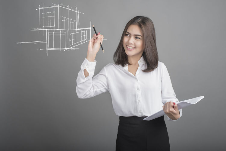 Adult Blackboard  Drawing - Activity Education Formula Front View Gray Background Holding Home Home Interior Indoors  Model Home One Person People Standing Studio Shot Women Writing Young Adult Young Women