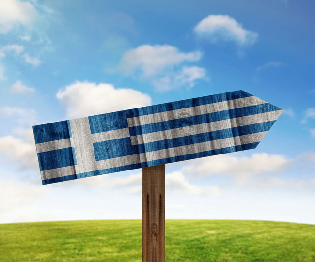Close-up of greek flag painted on wooden sign against sky