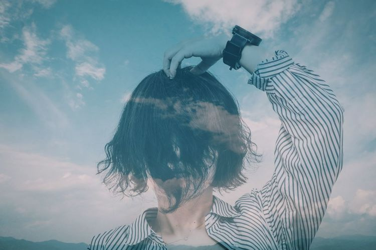 Multiple exposure of woman and cloudy sky
