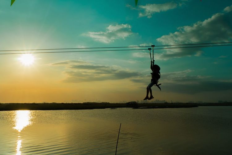Man Zip Lining Over Sea Against Sky During Sunset