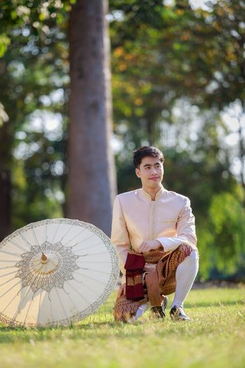 Smiling bridegroom wearing kurta while kneeling on grassy field