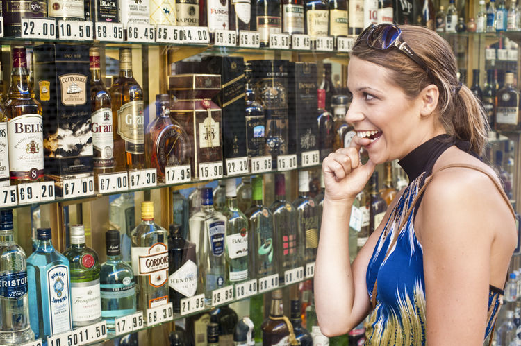 Young attractive tourist woman in the mediterranean Adult Adults Only Alcohol Beautiful Woman Bottle Cheerful Choice Day Drink Happiness Indoors  One Person One Woman Only One Young Woman Only Only Women People Perfume Perfume Counter Retail  Shelf Smiling Store Variation Women Young Adult