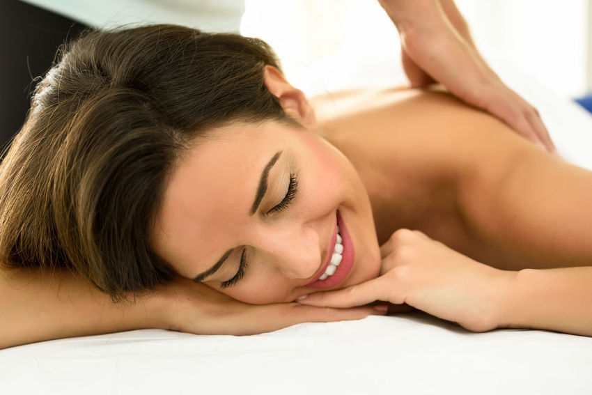 Young woman receiving a back massage in a spa center. Female patient is receiving treatment by professional therapist. Alternative Therapy Beautiful Woman Beauty Beauty Spa Beauty Treatment Body Care Comfortable Enjoyment Eyes Closed  Happiness Health Spa Human Body Part Human Hand Leisure Activity Lying Down Massage Table Massaging One Person Pampering Relaxation Smiling Spa Treatment Wellbeing Young Adult Young Women