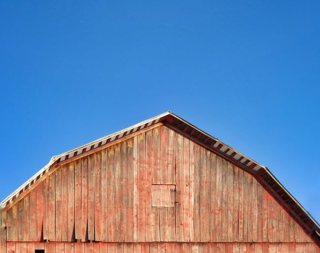Low angle view of old red building against clear blue sky