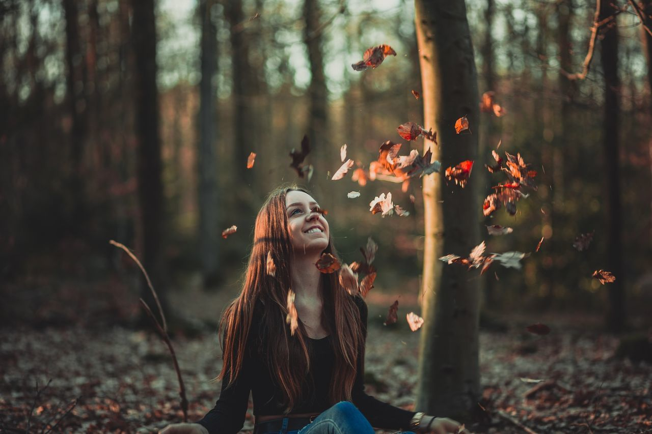 PORTRAIT OF SMILING YOUNG WOMAN IN FOREST DURING AUTUMN