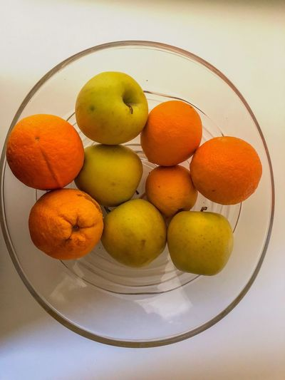 Bowl of fruits on a white table Food Food And Drink Fruit Wellbeing Freshness Citrus Fruit Indoors  Orange Color Still Life Orange - Fruit Orange Group Of Objects No People Table Bowl Directly Above Close-up High Angle View Group