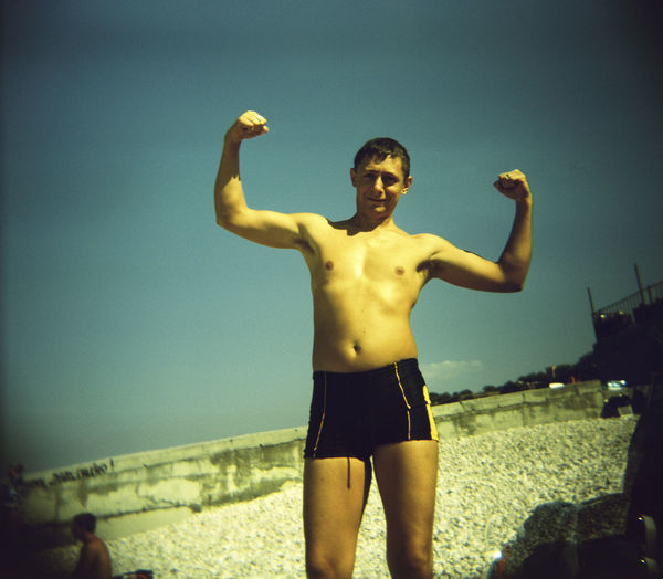 Shirtless mature man flexing muscles while standing against sky during sunny day