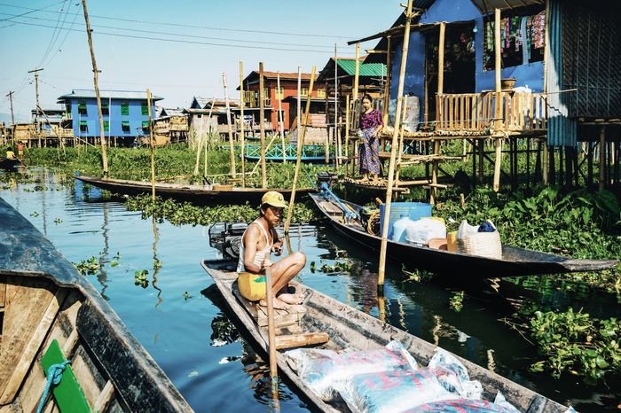 Nautical Vessel Transportation Mode Of Transport Building Exterior Boat Architecture Water Day Built Structure Canal Outdoors Moored Sitting Stilt House Men Gondola - Traditional Boat Real People Clear Sky Adult One Person The Street Photographer - 2017 EyeEm Awards Inle Lake Myanmar