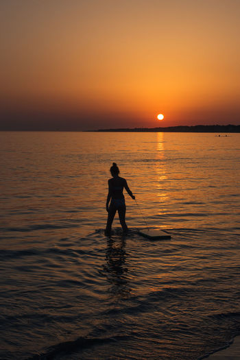 Silhouette girl wading in sea against sky during sunset