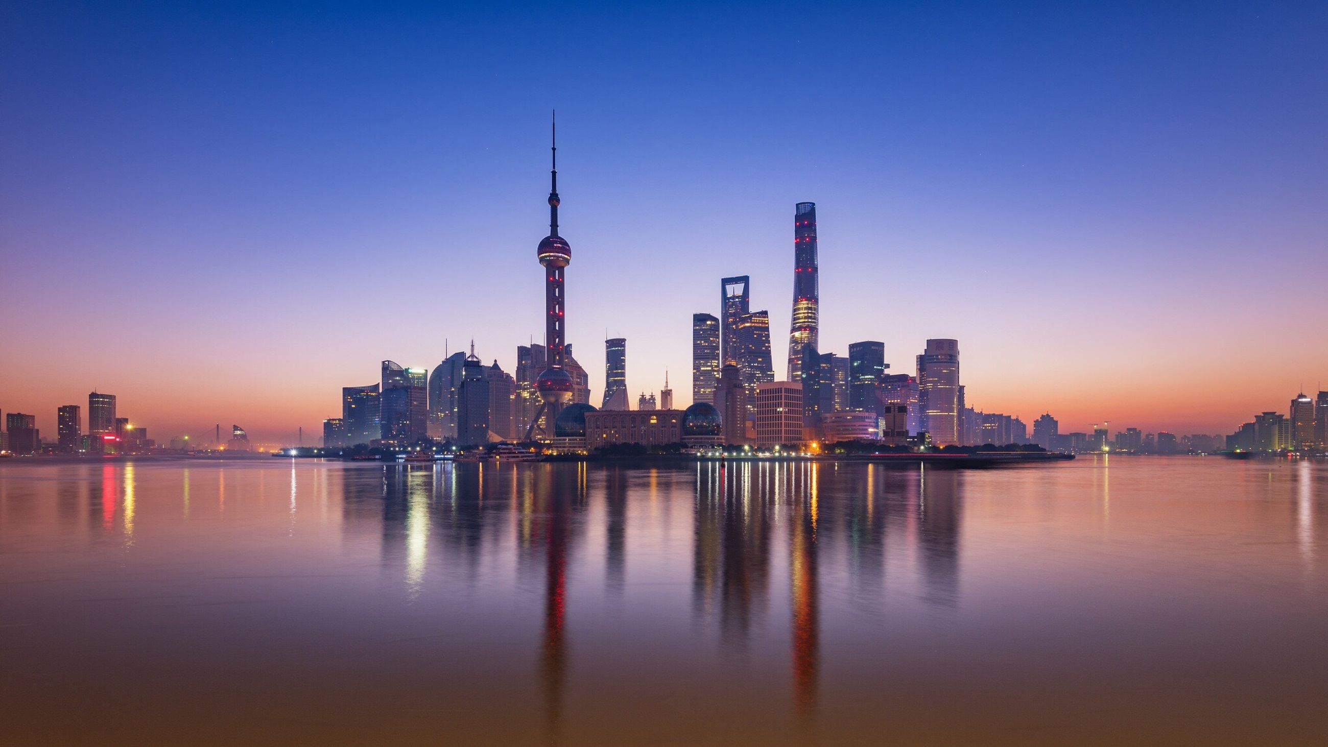 city, architecture, skyscraper, building exterior, reflection, modern, urban skyline, cityscape, built structure, sunset, tower, travel destinations, sea, outdoors, water, no people, sky, illuminated, downtown district, night